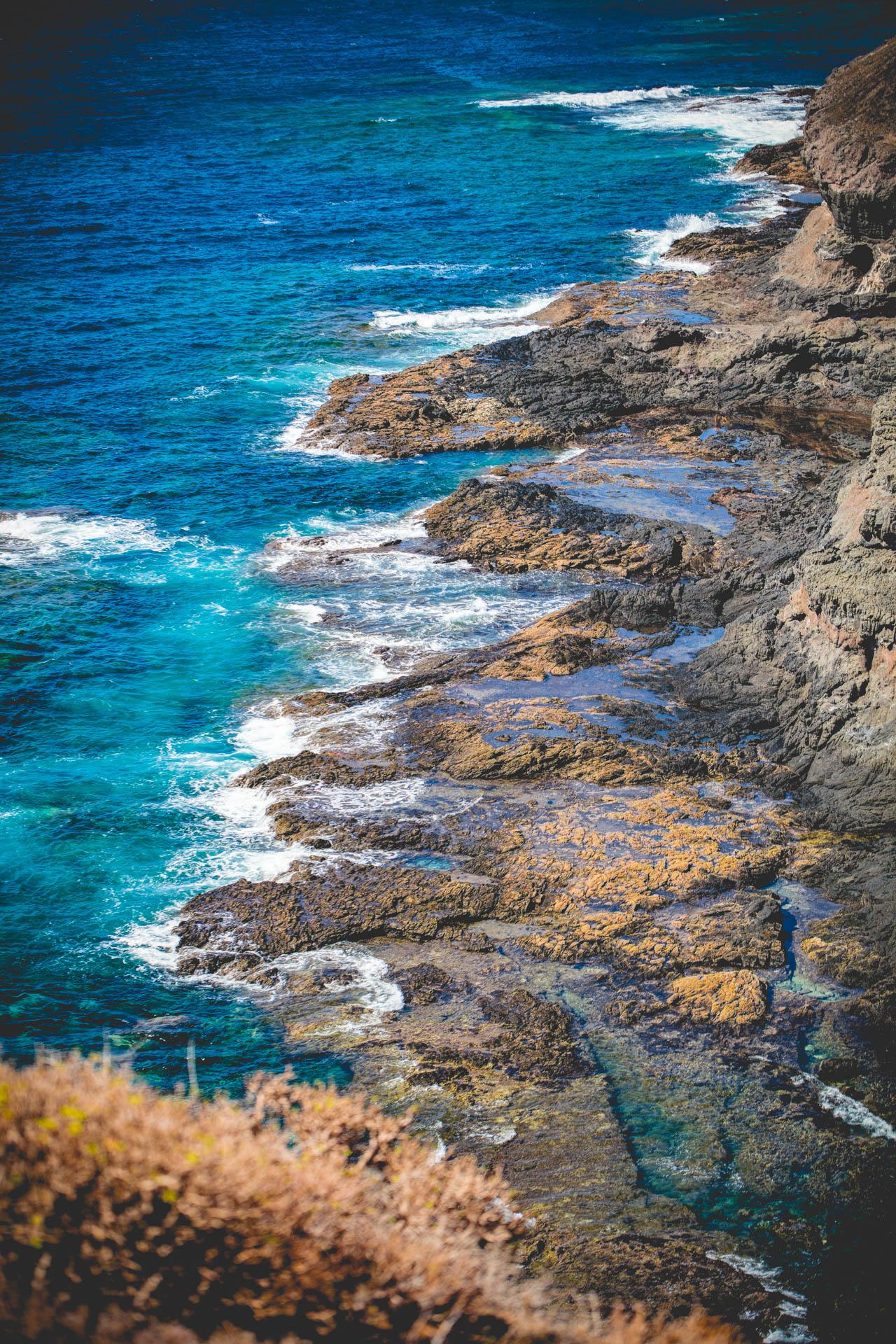 Der schwarze Felsstrand Playa la Caleta auf Gran Canaria mit tiefblauem Atlantik und tosenden Wellen