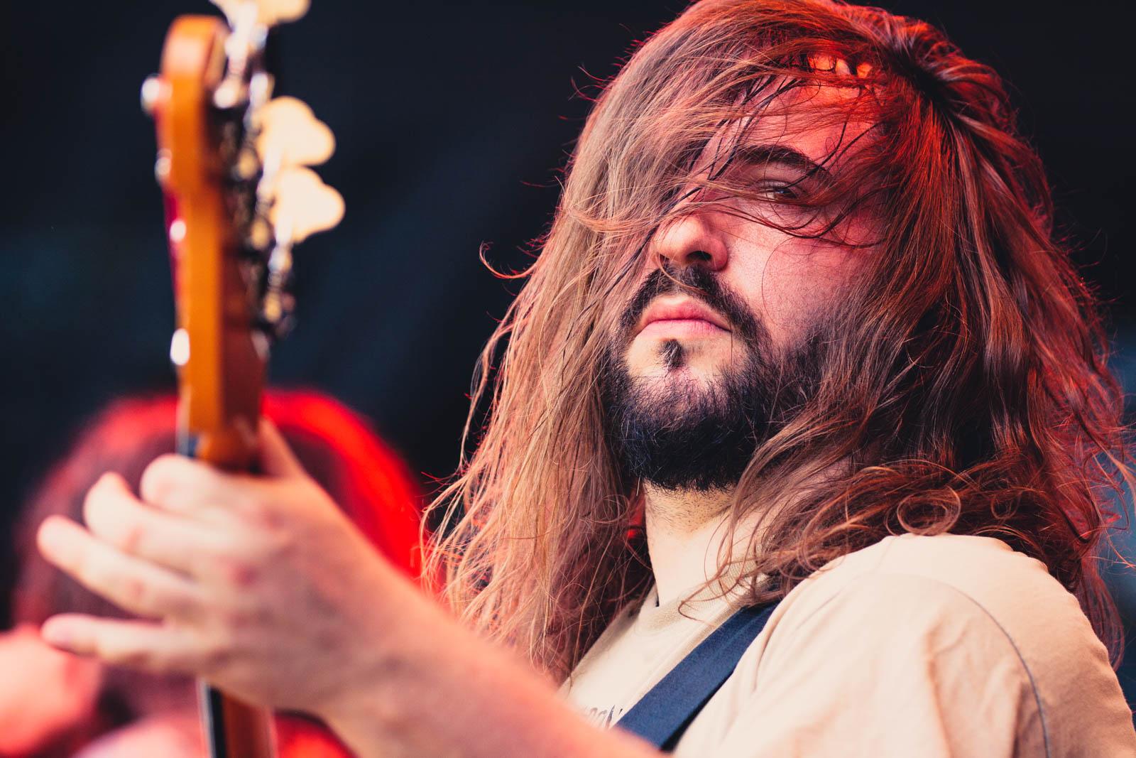 Bassist bei einem Live Aufritt 2014, die langen Haare verdecken das Gesicht